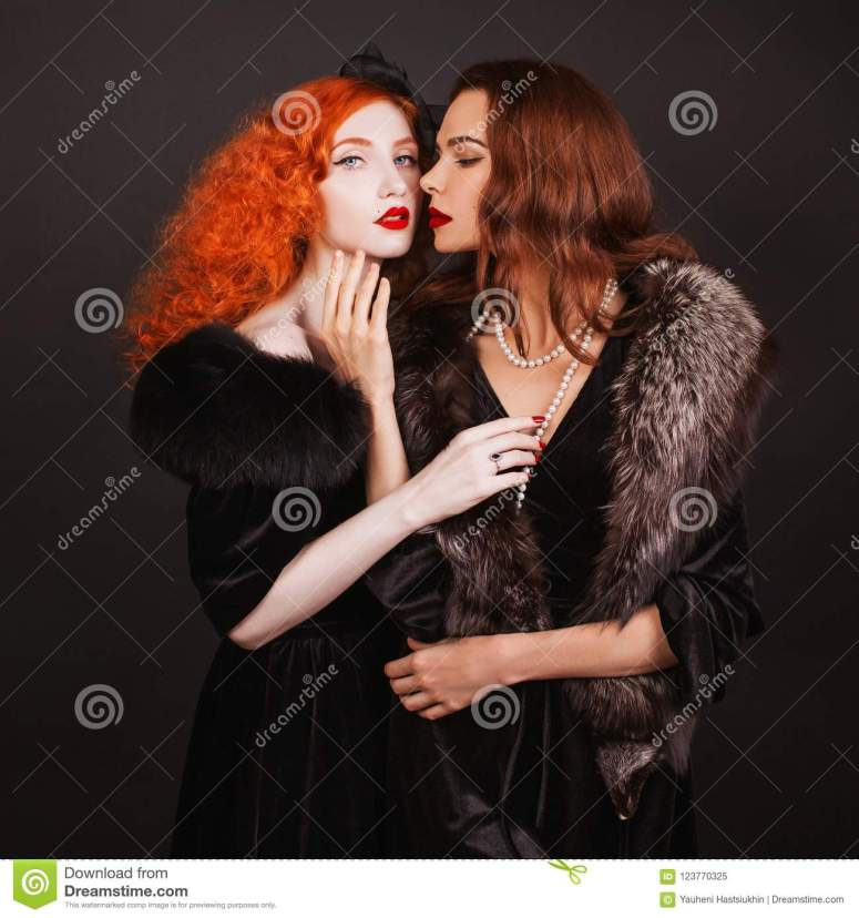 two-young-lesbian-women-curly-long-hair-black-dress-touch-each-other-brutal truth